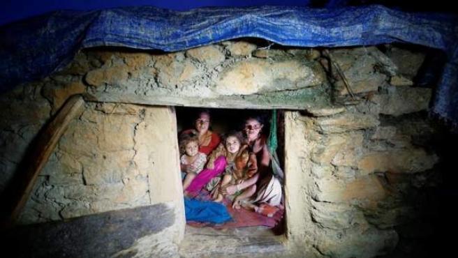 Foto de Pabitra Devi Jaisi (dcha), de 29 años, y de Sarada Jaisi (izq), de 30, mientras comparten un pequeño cobertizo 'Chapuadi' con sus hijos.