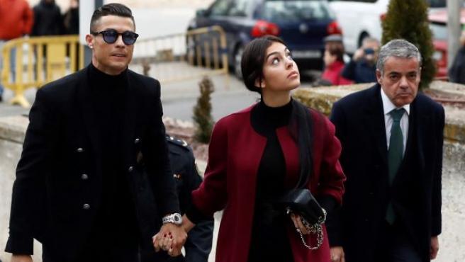 El exjugador del Real Madrid Cristiano Ronaldo (i), junto a su pareja Georgina Rodríguez, a su llegada este martes a la Audiencia Provincial de Madrid.