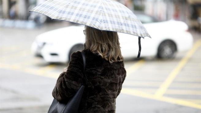 Imagen de archivo de una persona con paraguas por la lluvia.