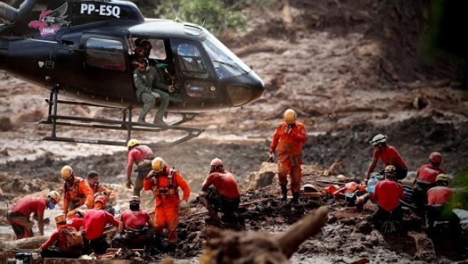 Bomberos y miembros de la policía civil trabajan en el rescate de los cuerpos de las víctimas de la ruptura de la presa minera.