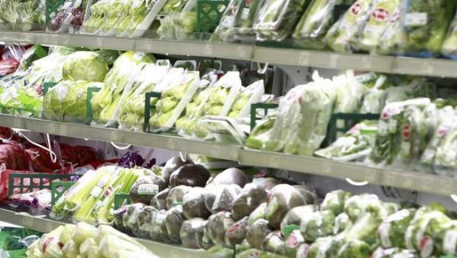 Un supermercado con bandejas de verdura.