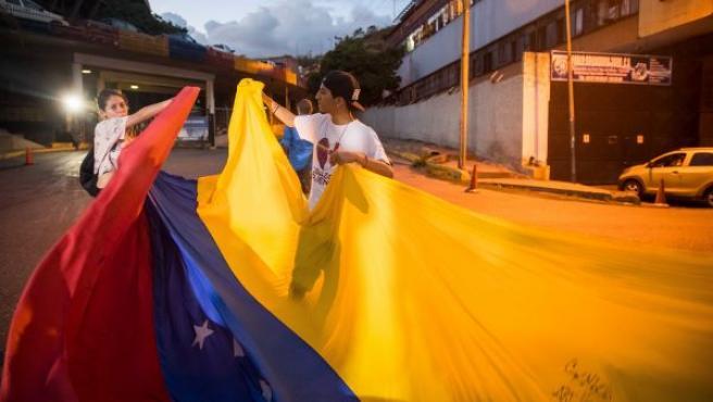 Ciudadanos venezolanos portando una bandera de Venezuela.
