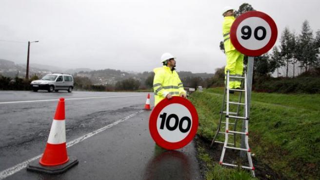Dos operarios retiraban la última señal en Galicia de velocidad máxima permitida en las vías convencionales, la cual han sustituido por la nueva limitación a 90 km/h.