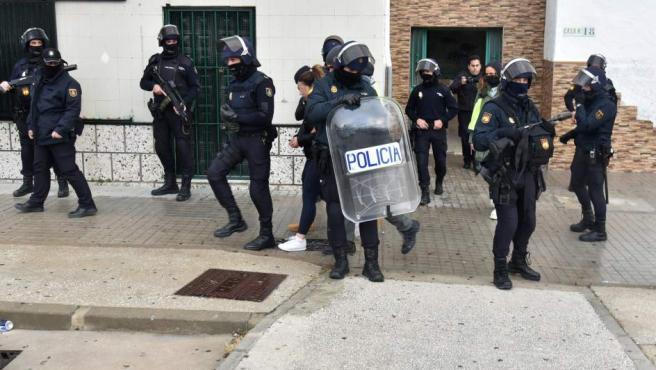 """Agentes de la Policía Nacional salen con una detenida en un bloque de la barriada gaditana del Saladillo en Algeciras, en la operación bautizada como """"Lupita""""."""