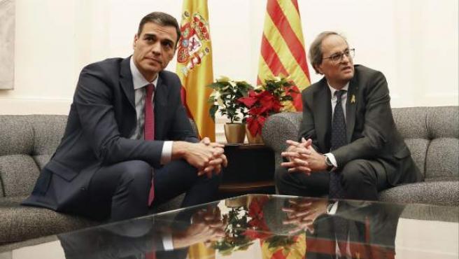 El presidente del Gobierno, Pedro Sánchez, y el de la Generalitat, Quim Torra (d), durante la reunión que mantienen esta noche en el Palau de Pedralbes de Barcelona, con la asistencia de algunos ministros y consellers.
