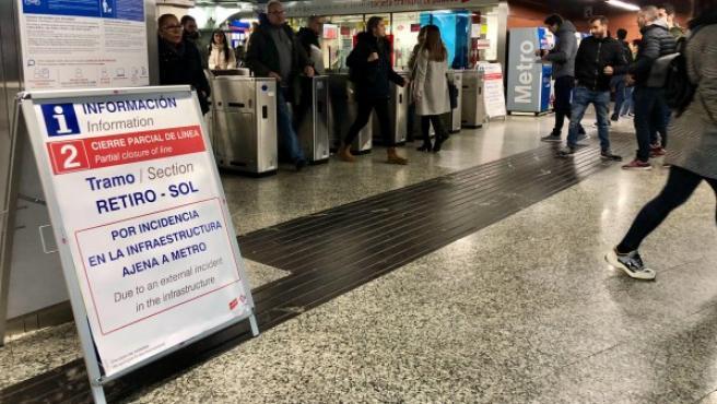 """En la entrada al metro de Sol, un cartel informa: """"Cierre parcial de la línea 2 por incidencia en la infraestructura""""."""