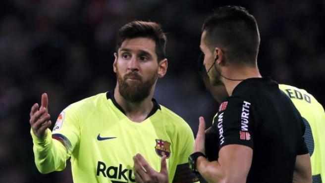 Messi conversa con un árbitro durante un partido del Barcelona.