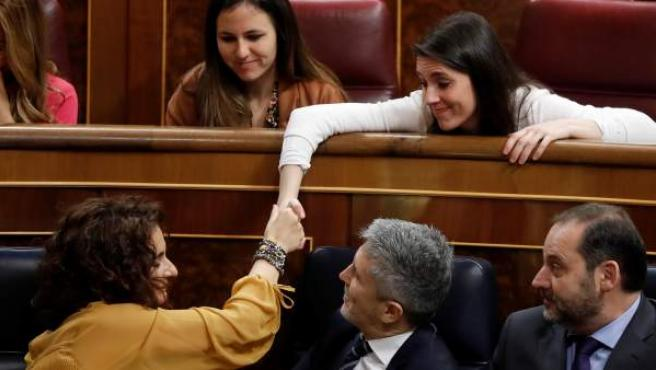 La ministra de Hacienda, María Jesús Montero (i - 1ªfila), estrecha la mano con la portavoz de Podemos en el Congreso, Irene Montero (d - 2ª fila).