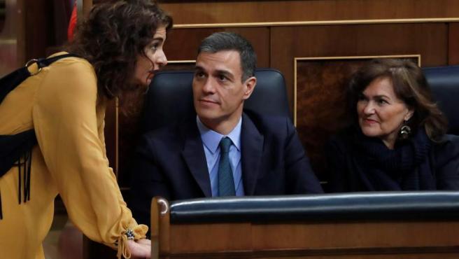 La ministra de Hacienda, María Jesús Montero (i), conversa con el presidente del Gobierno, Pedro Sánchez, y la vicepresidenta, Carmen Calvo (d).