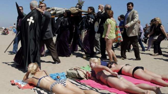 Miembros de las distintas cofradías y público se mezclan durante la procesión a la playa de la Semana Santa Marinera, en Valencia.