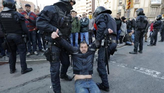 Efectivos de los Mossos d'Esquadra desalojan a uno de los huelguistas que cortan la Carrer de Sants de Barcelona.