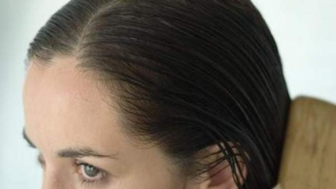 Una mujer se cepilla el pelo tras lavárselo.