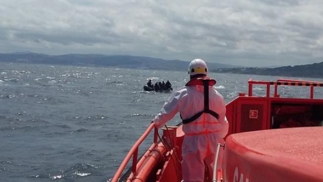 Un operario de Salvamento Marítimo y una patera al fondo en una imagen de archivo.