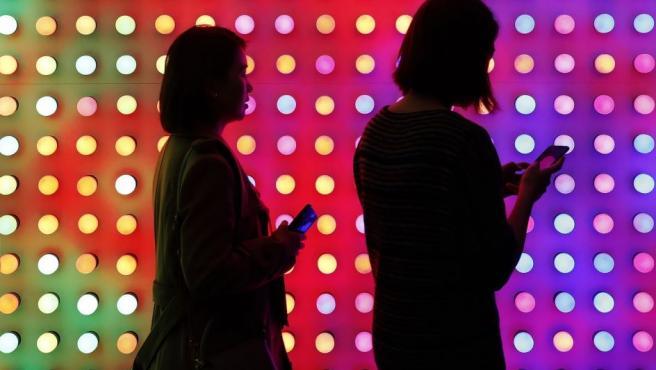 Dos visitantes conversan en uno de los rincones más coloridos del Mobile World Congress, frente a un juego de luces del 'stand' de la multinacional china Xiaomi.