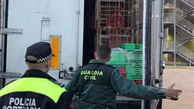 Agentes de la Guardia Civil y la Policía Portuaria, durante el rescate de un inmigrante que se encontraba semiinconsciente en un contenedor en el puerto de Melilla.