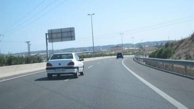 Un coche circula por el carril izquierdo en una vía de dos carriles.