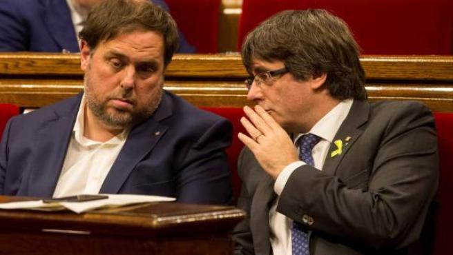 Puigdemont conversa con Junqueras durante una sesión del Parlament.