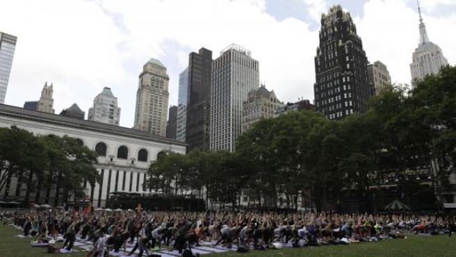 Decenas de personas participan en una clase de yoga, en Bryant Park, en Nueva York (EE.UU).