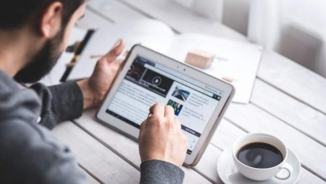Un hombre navega por internet con su tableta.