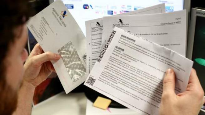 Un hombre revisa documentos de la Agencia Tributaria