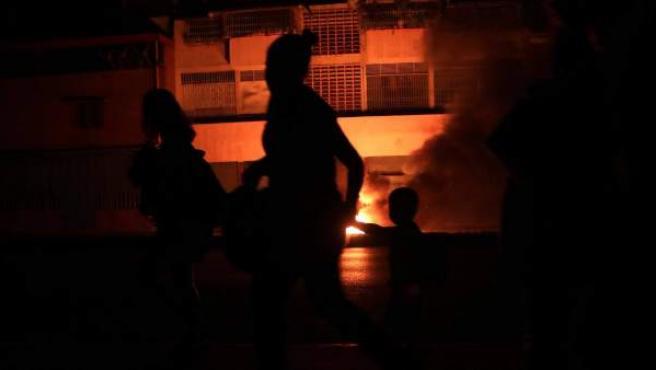 Transeúntes en una calle a oscuras por el apagón eléctrico en Caracas (Venezuela).