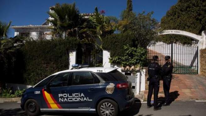 Dos agentes de la Policía Nacional custodian la vivienda de Estepona donde una mujer de 58 años ha sido apuñalada por su marido.