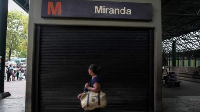 Una mujer camina frente a una estación cerrada del Metro de Caracas, fuera de funcionamiento debido al apagón eléctrico afectó a toda Venezuela.
