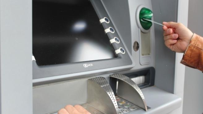 Una persona saca dinero de un cajero automático, en una imagen de archivo.