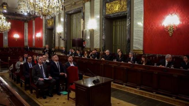"""Junqueras (d); Romeva (c) y Forn (i), junto al resto de los líderes independentistas, en el banquillo del Tribunal Supremo al inicio del juicio del """"procés"""". A la derecha, los letrados de las defensas."""