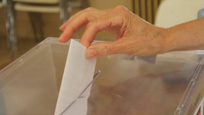 Una persona introduce una papeleta en una urna electoral, en una imagen de archivo.