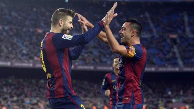 Xavi Hernández y Gerard Piqué celebran un gol del FC Barcelona.