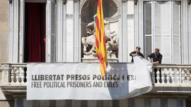 """Imagen del momento en el que retiran la pancarta, en favor de los """"presos políticos"""", de la Generalitat."""