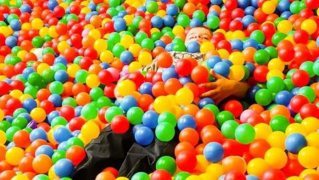 Imagen de un niño en un parque de bolas.