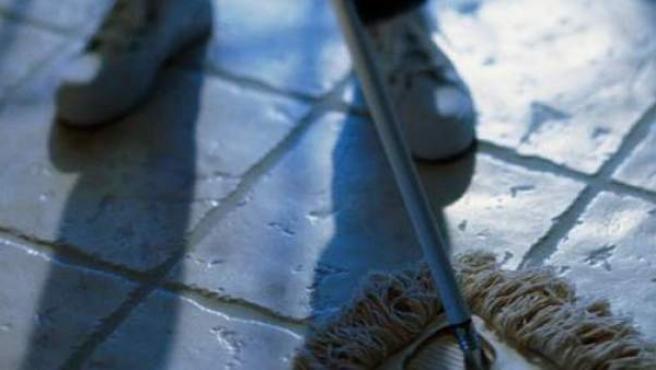 Una persona, fregando el suelo de una casa.