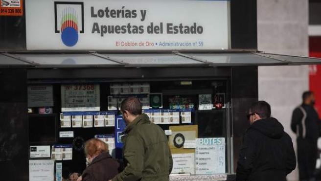 Varias personas compran décimos de lotería para el Sorteo del Niño.