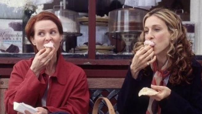 Miranda Hobbes y Carrie Bradshaw se comen unos cupcakes delante de Magnolia Bakery.