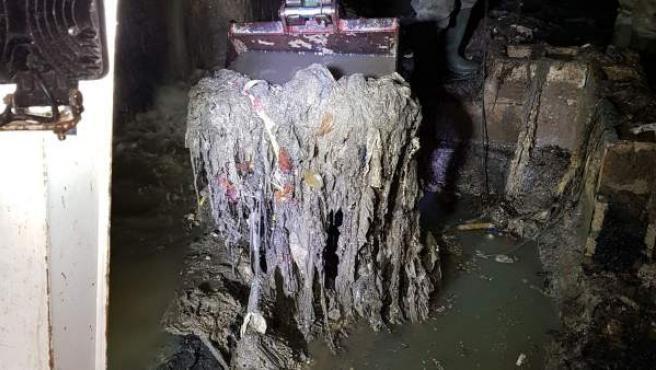 Labores de extracción de las toneladas de residuos acumulados en el colector norte de València.