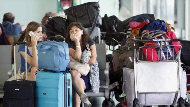 Algunos viajeros esperan la salida de sus vuelos en la Terminal 1 del Aeropuerto de El Prat, en Barcelona.