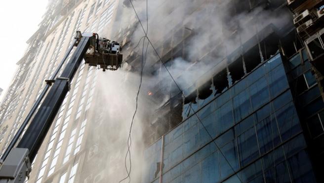 Miembros del cuerpo de bomberos de Bangladesh intentan apagar el incendio que se ha producido en un rascacielos de Dacca.