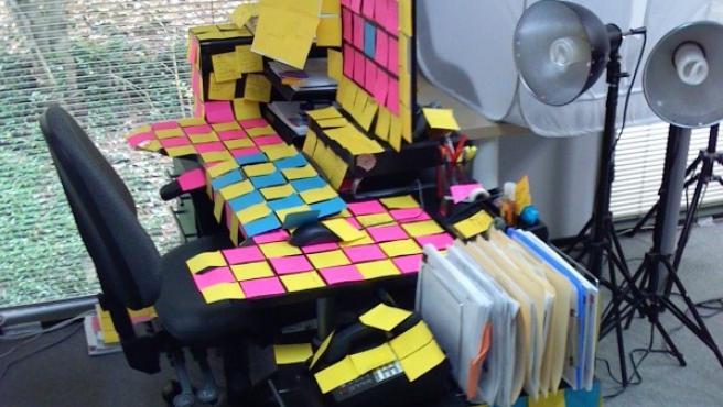 Un escritorio envuelto de 'post-it' que bien podría formar parte del April Fool's Day.