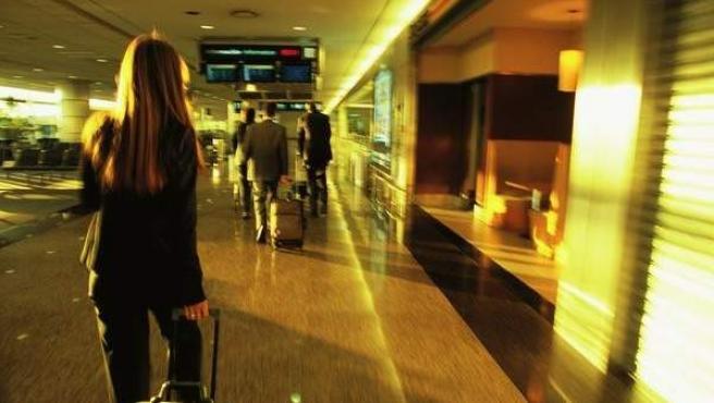 Varias personas se desplazan con sus maletas por un aeropuerto, en una imagen de archivo.