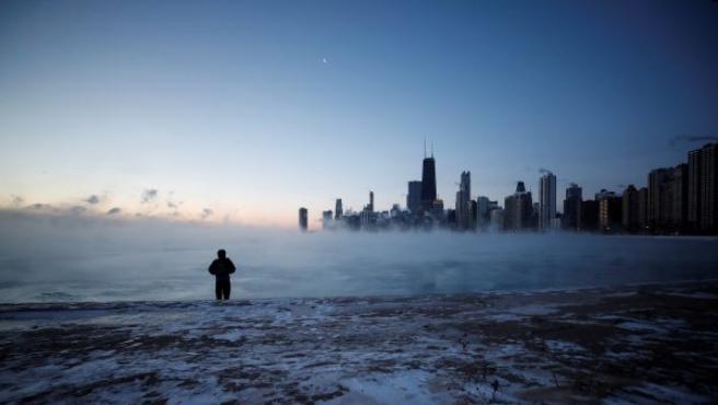 Un hombre camina por la playa, completamente congelada, de la Avenida Norte al amanecer, en el lago Michigan en Chicago (EE UU).