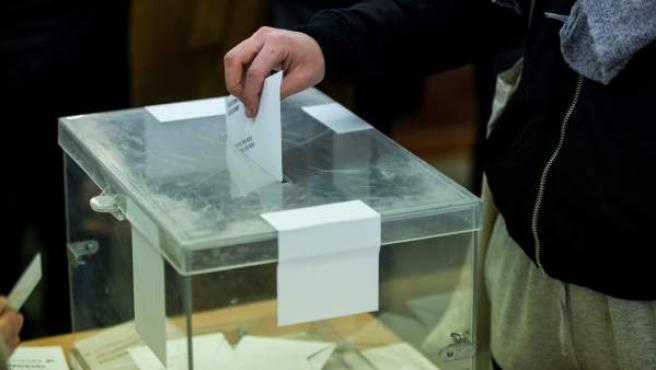 Un ciudadano deposita su voto en la urna en el colegio electoral Narcís Monturió de Barcelona.