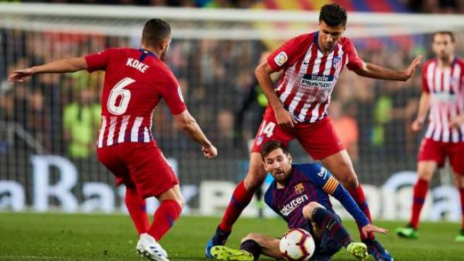 Messi pelea una pelota con Koke y Rodri.
