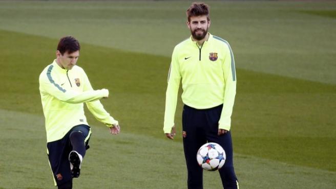 Los juagdores del FC Barcelona Lionel Messi (izda) y Gerard Piqué entrenan con el equipo en el estadio Parc des Princes de París.