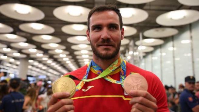 Saul Craviotto enseña sus medallas de Río 2016 a la llegada a España