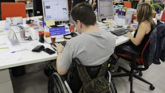 Una persona con una discapacidad, en su puesto de trabajo.