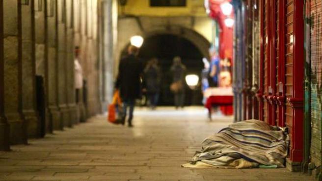 Una persona sin hogar durmiendo en los soportales de la Plaza Mayor.