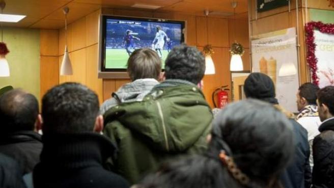 Varias personas viendo fútbol en una televisión.