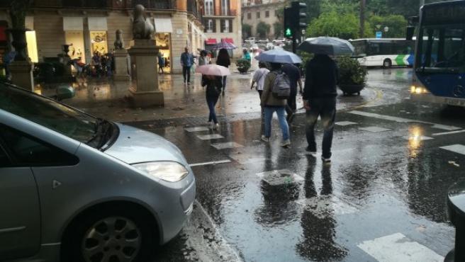 Imagen de archivo de gente caminando bajo la lluvia.